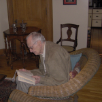 Man sitting in a chair, reading a book inside