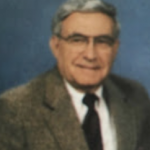 Man smiling in glasses and a suit