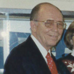 Man smiling in a suit with glasses