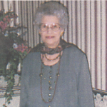 Woman wearing glasses, standing, smiling