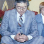 Man in glasses wearing a suit, sitting on the ground