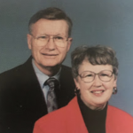 Man and woman smiling, both in glasses