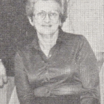 Woman smiling, wearing glasses