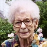 Woman wearing glasses and a colorful shirt, outside