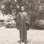Woman wearing a graduation cap and gown, standing outside in front of a tree
