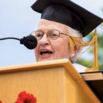 Woman with a graduation cap talking into a microphone at a podium