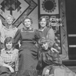 Group of women, smiling, wearing long dresses, in front of a hanging quilt