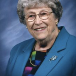 Woman smiling in a blazer with glasses
