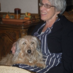 Woman wearing glasses sitting and smiling with a dog in her lap