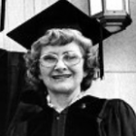 Woman wearing a cap and gown, smiling, with glasses