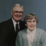 Man and woman wearing glasses, smiling