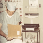 A male doctor reading from a paper, wearing doctor's scrubs