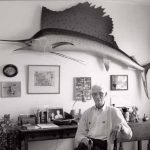 Man sitting at a desk with a large swordfish above, on the wall