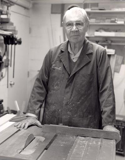 "Man wearing a coat with ""Everett"" on it at a working bench with a saw in it"