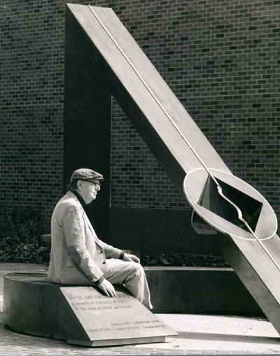 Man sitting outside in profile, looking at a large sculpture