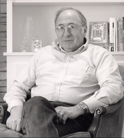 Man sitting in a chair, with glasses