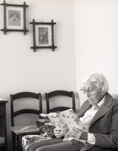Woman sitting on a coach looking at a book