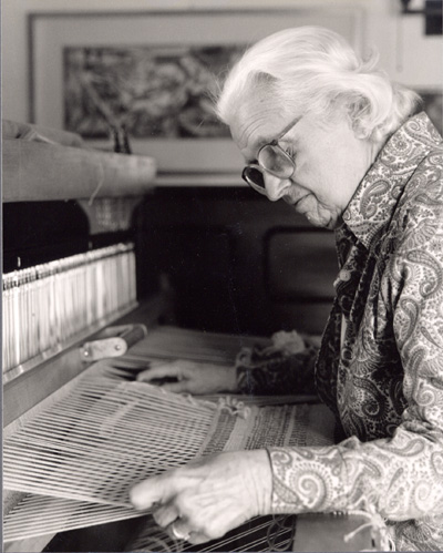Woman sitting at a weaving loom, looking down