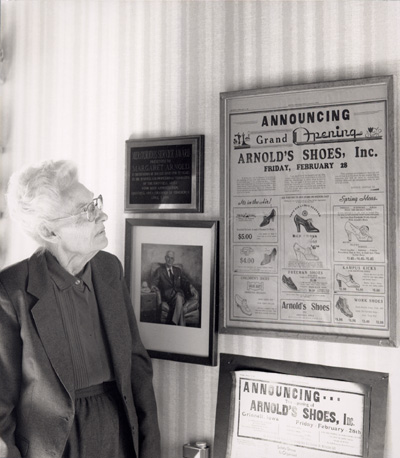 "Woman looking at a framed newspaper on the wall with ""Arnold's Shoes, Inc."" in large text"