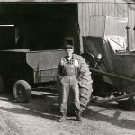 Man in overalls standing outside in front of a tractor