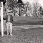 "Man standing, outside, by the sign ""Dick Sears Auctioneer Grinnell IA"""