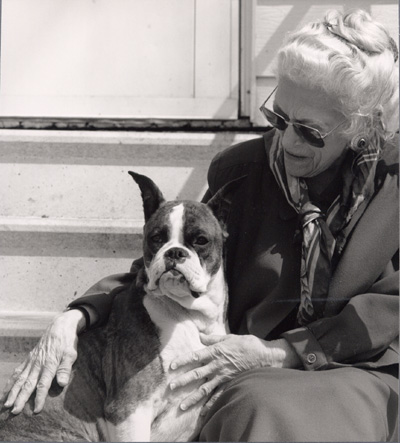 Woman and a boxer dog, sitting outside