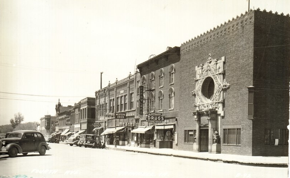Black and white photo of businesses and cars