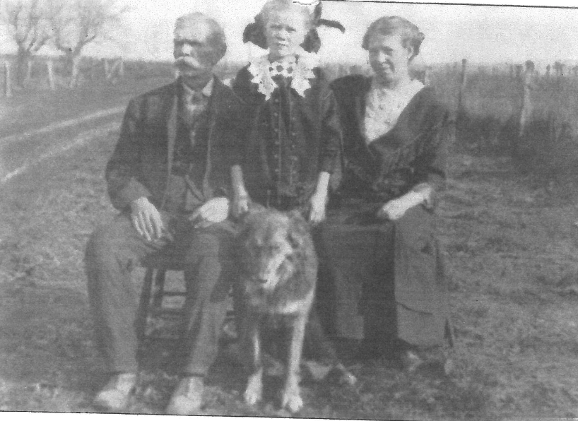 Black and white photo of an man, child, woman, and dog
